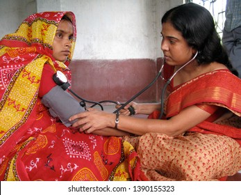 Diamond Harbour, West Bengal - December 4, 2008: A woman health worker from a charity visited house in a village to check blood pressure of a  pregnant mother as part of antenatal checkup.