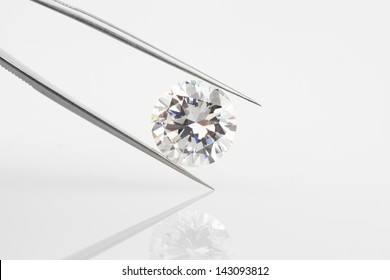 Diamond held within tweezers. Large round diamond, angled and reflected on pale background.