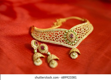 Diamond jewelry placed on red cloth with ear rings