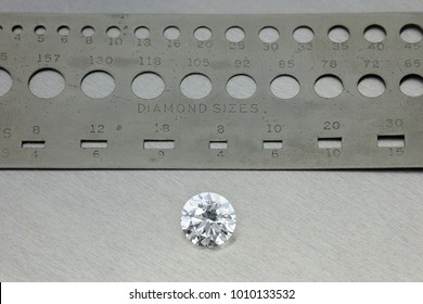 Diamond Measurement ruler : loose brilliant 4 carats diamond, next to a diamond size silver ruler with holes in background bright