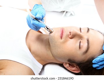 Diamond Microdermabrasion, man to a beautician.Handsome man during microdermabrasion treatment in beauty salon