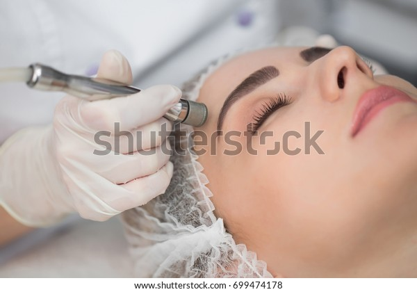 Diamantmikrodermabrasion, kosmetisches Peeling. Frau während einer Behandlung mit Mikrodermabrasionen im Schönheitssalon