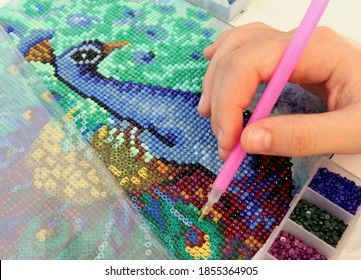 Diamond mosaic painting fragment of making close-up top view, handmade hobby.