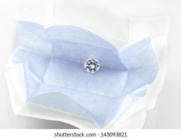 Diamond in open diamond parcel. Round brilliant cut loose diamond in blue parcel paper.