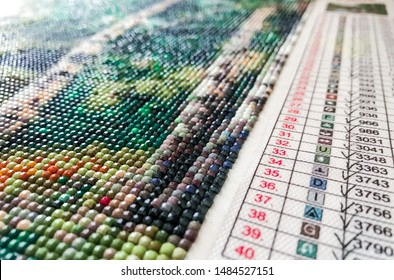 Diamond painting embroidery craft. Acrylic rhinestones.Table with numbers, color matching. Close up, selective focus