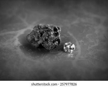A diamond and a piece of coal on a slate background