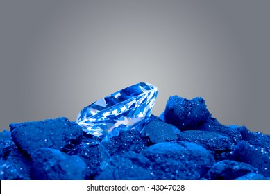 A diamond in a pile of coal shows a long awaited precious gem evolve.  Image was shot using blue backlighting to give it a special effect.