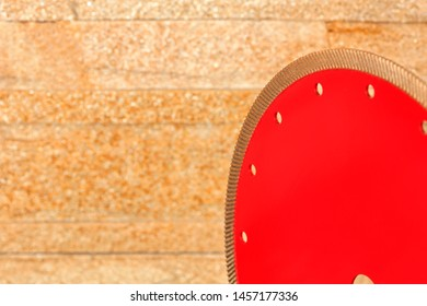 Diamond red cutting segment against a golden sandstone wall close-up, copy space for text.