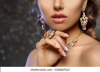 Diamond ring on the hand of a beautiful woman. Brilliant.  Antique old vintage earrings and ring. Jewelry on girl finger with lux manicure