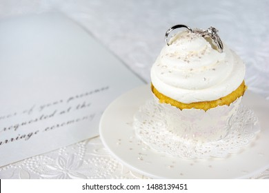 diamond ring and silver wedding band in cupcake icing on formal invitation