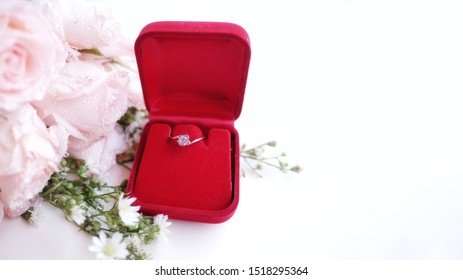 A diamond ring, wedding ring, is in the red box and pale peach roses for background. The moment of wedding day, anniversary, engagement or valentine's day. Happy sweetest day.