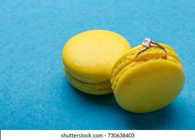 A diamond ring in yellow macaroon on blue background. the offer to marry. place for text