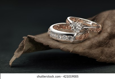 Diamond rings, overlapping male and female, set on leaf harmonizing the ring design and color.