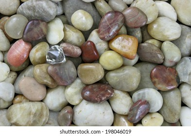 Diamond in the Rough; Natural colored small smooth rocks background with copy space