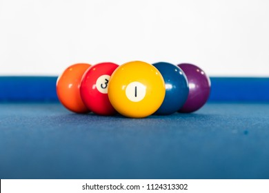 diamond shape of 9-ball pool balls placed in rack position on blue felt table, focus on number one, close up