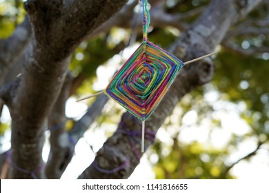 Diamond shaped yarn weaving called God's Eyes ornaments hanging from tree branch. Originated in Mexico's Huichol Indians called Ojo de Dios in Spanish.