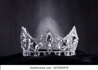 Diamond Silver Crown for Miss Pageant Beauty Contest, Crystal Tiara jewelry decorated gems stone and abstract dark background on black velvet fabric cloth, Macro photography copy space for text logo