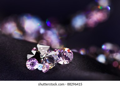 Diamond (small purple jewel) stones heap over black silk cloth background