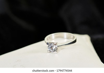 Diamond solitaire ring on small white stones on black background