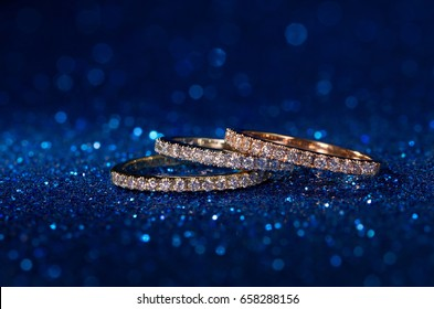 diamond stacked rings on blue glitter sparkle blue background,white gold,yellow gold,rose gold