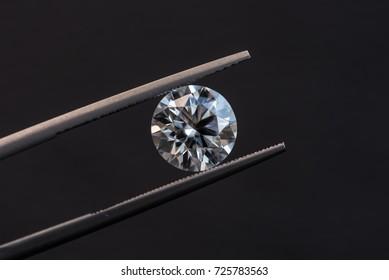 Diamond in tweezers hearts and arrows
