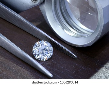 Diamond with tweezers and magnifier loupe.