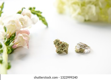 Diamond Wedding and Engagement Ring on Marijuana Bud with Pink Flowers Close Up - Cannabis Wedding