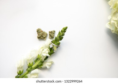 Diamond Wedding and Engagement Ring on White Flower with Marijuana Buds Top Down - Cannabis Wedding