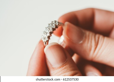 The diamond wedding ring is on the woman's finger. To be a future bride, closeup of daimond selective focus and with a very shallow depth of field, with copy space.