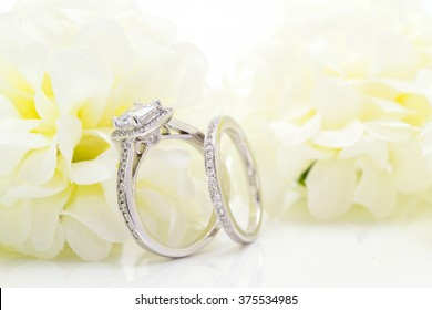 Diamond white gold ring. White Flower background