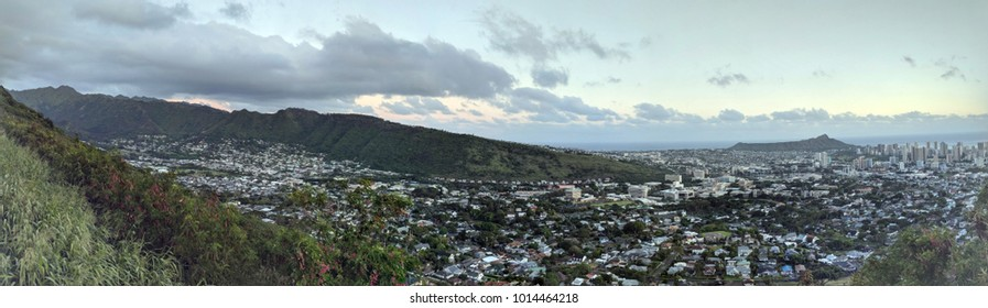 Diamondhead and the city of Honolulu, Kaimuki, Kahala, and oceanscape on Oahu on a nice dayviewed from high in the mountains with tall trees in the foreground.