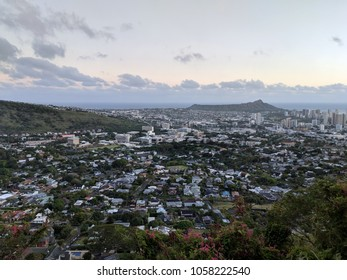 Diamondhead and the city of Honolulu, Kaimuki, Kahala, and oceanscape on Oahu on a nice day at dusk viewed from high in the mountains with tall trees in the foreground. Taken on November 23, 2017.