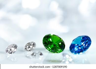 Diamonds, blue sapphire and green emerald brilliant cut jewels, sparkle background