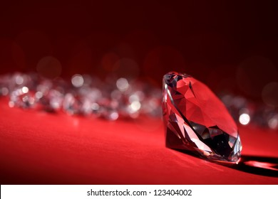 Diamonds on red background with focus on one in foreground