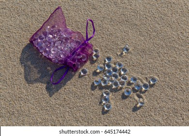 Diamonds in a small purple bag on the sandy dune
