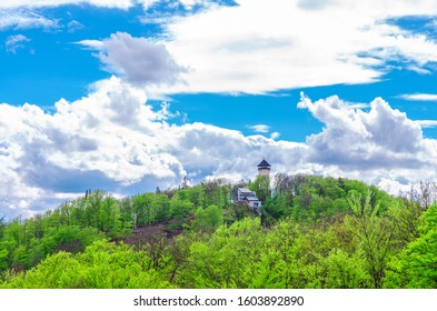 Diana Observation Tower (Rozhledna Diana) and funicular on hill above Slavkov Forest with green trees and Karlovy Vary (Carlsbad) town, blue sky white clouds background, West Bohemia, Czech Republic