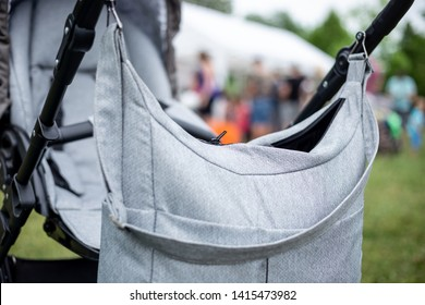 A diaper bag is hanging on stroller in the Park