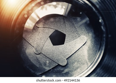 The diaphragm of old camera lens aperture with warm light bokeh. Selective focus with shallow depth of field. Vintage color tone filtered. Abstract texture background.