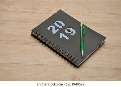 A diary for 2019 and a pencil on a wooden background