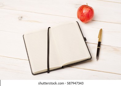 Diary, apple and pen on rustic wooden table