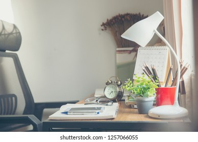 Diary and book student to study for exam. Wooden desk with desktop laptop, notebook, book, pencils, diary, notepad, clock ,and white lamp, working space at home. Desk for student concept.