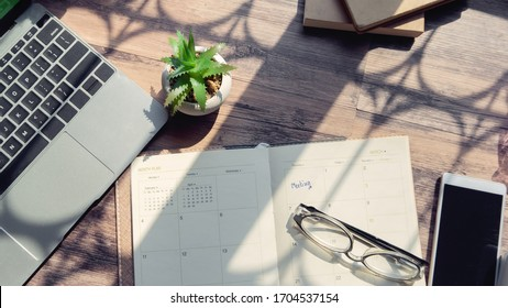 Diary and Calendar for Planner to management daily agenda, appointment and timetable for a job. Laptop smartphone glasses cactus and diary placed on office desk. Working online at home Concept.
