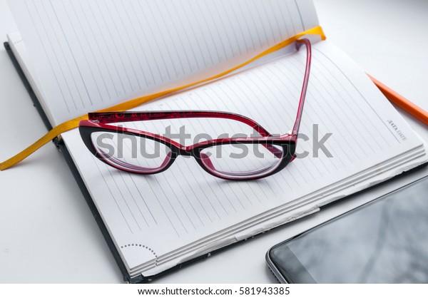 Diary, glasses, orange a pencil and smartphone