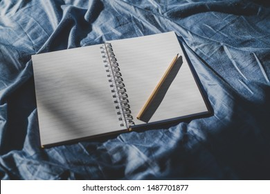 diary notebook on blue bedding; concept of journaling or brainstorming in the morning