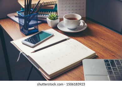 Diary and notebook for Planner to plan agenda, reminder, timetable, daily appointment, management on table. Calender, laptop, smartphone and cup of coffee place on office desk. work online at home