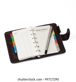 """A diary opened at page of """"Notes"""" with pen that lay on it. Isolated on white background"""