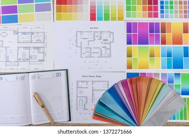 Diary with pen and color swatch on house plan in office