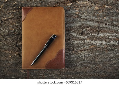 Diary and pen on a wooden old background top view