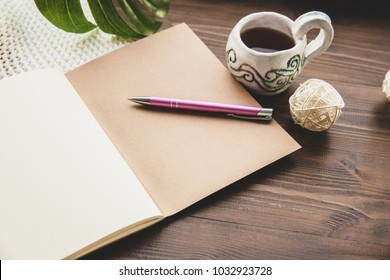Diary and pen on a wooden table at home. A cup of tea or coffee for breakfast, a notebook and a pink ball pen. Knitted plaid, diary, rattan ball and metal pen, place for text