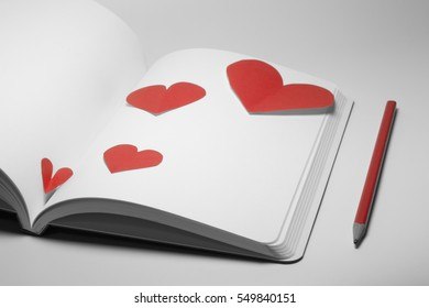 diary and pencil with paper heart on white background